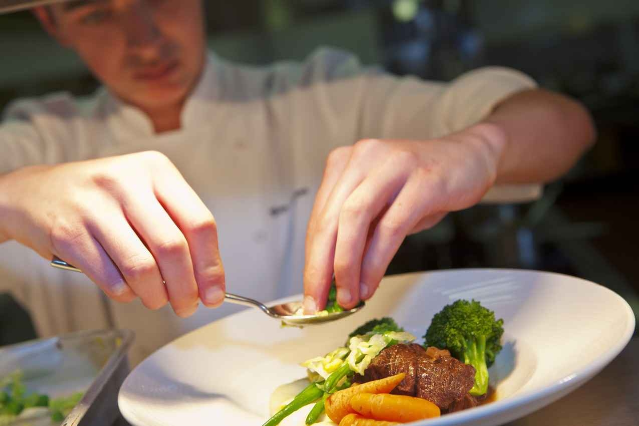 An experienced chef portioning a plate at one of the best all-inclusive resorts in Playa Del Carmen.