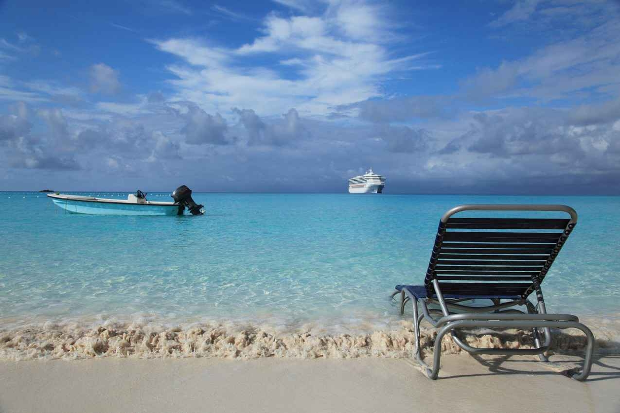 A Caribbean beach with a fishing boat and a cruise ship in the background.