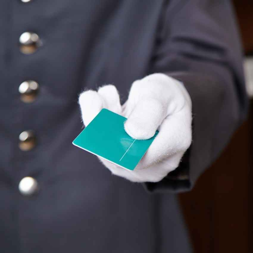 A bellboy handing a guest a key card.