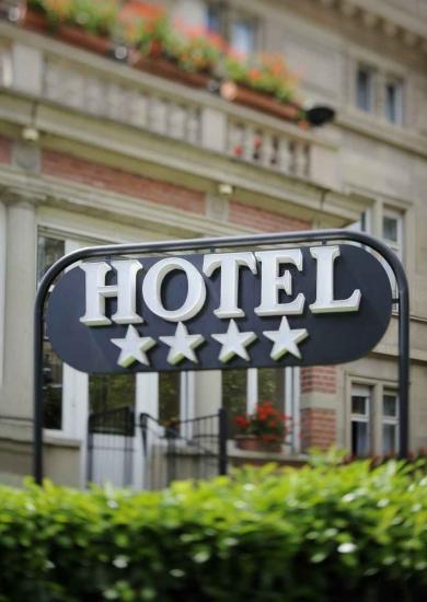 A four-star hotel sign on a street in Playa Del Carmen.