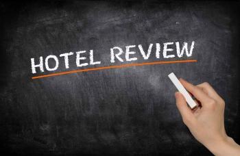 A hotel review written by hand on a black chalkboard.