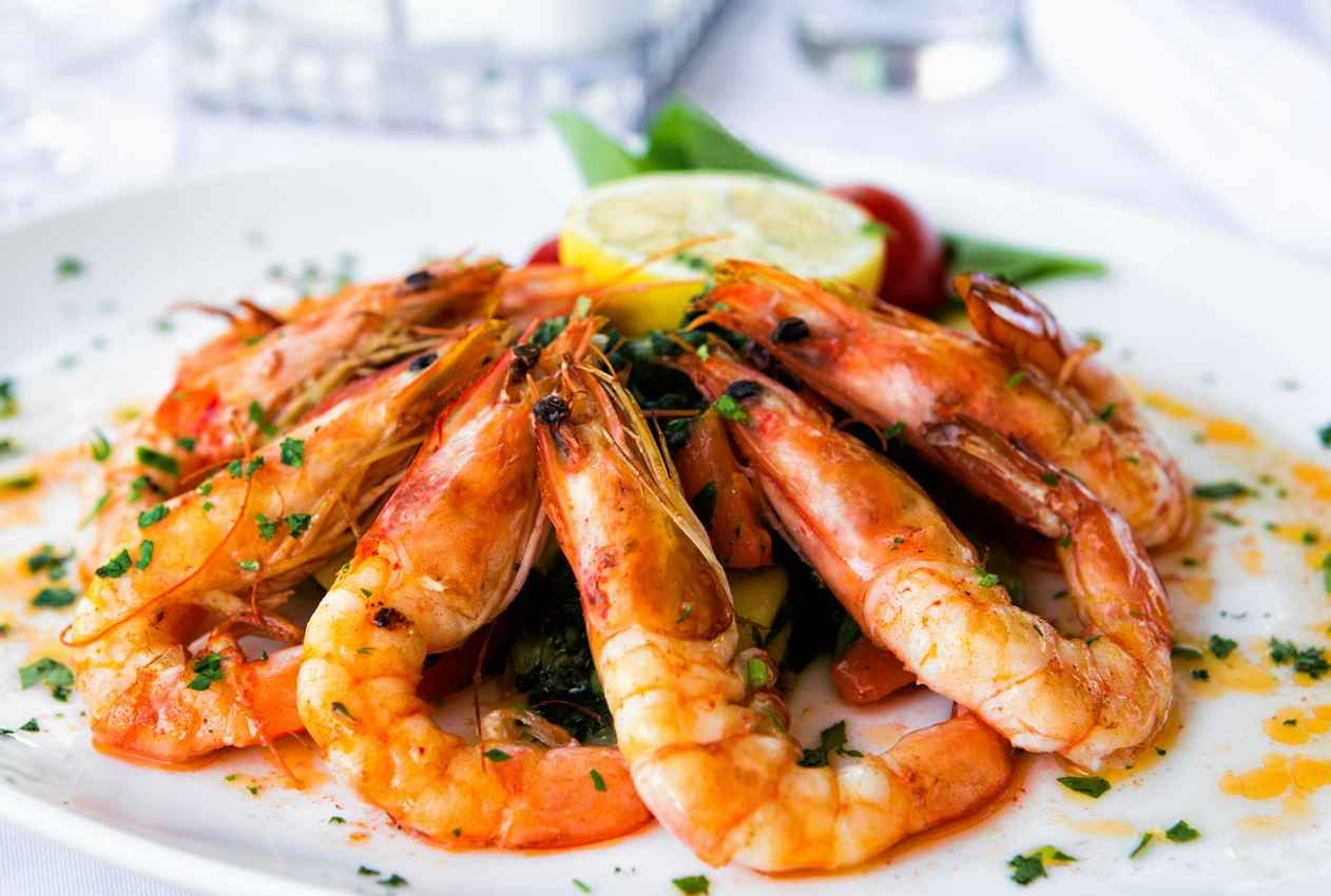 A plate full of decorative cooked shrimp with lemon in the center and seasoning on top.