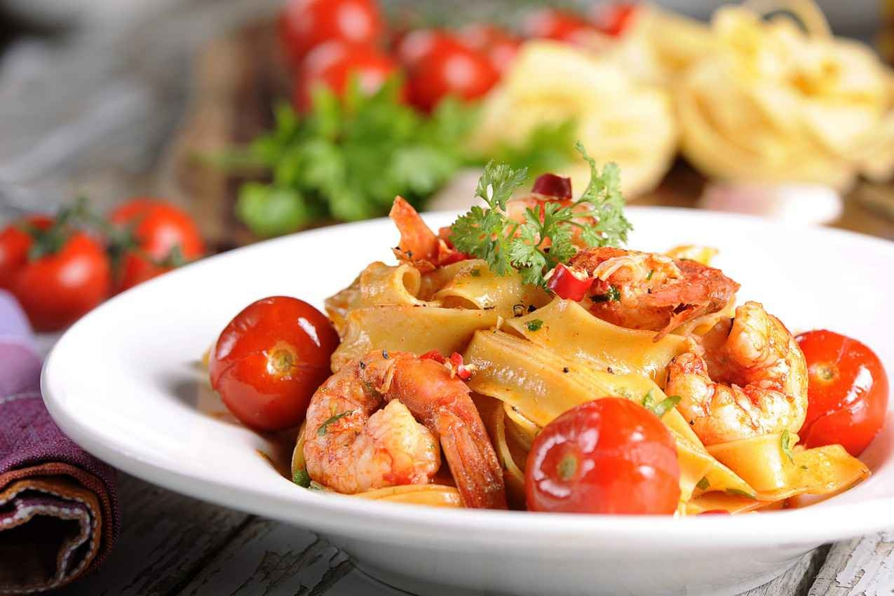Seafood pasta served with sliced cherry tomatoes.