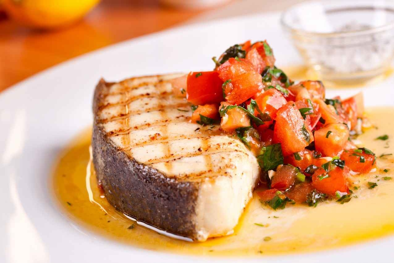 A seafood steak with oil and salsa on a plate at a great local restaurant.