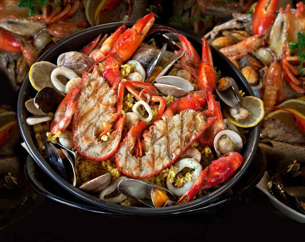 A pan full of cook seafood ready to be served to customers.