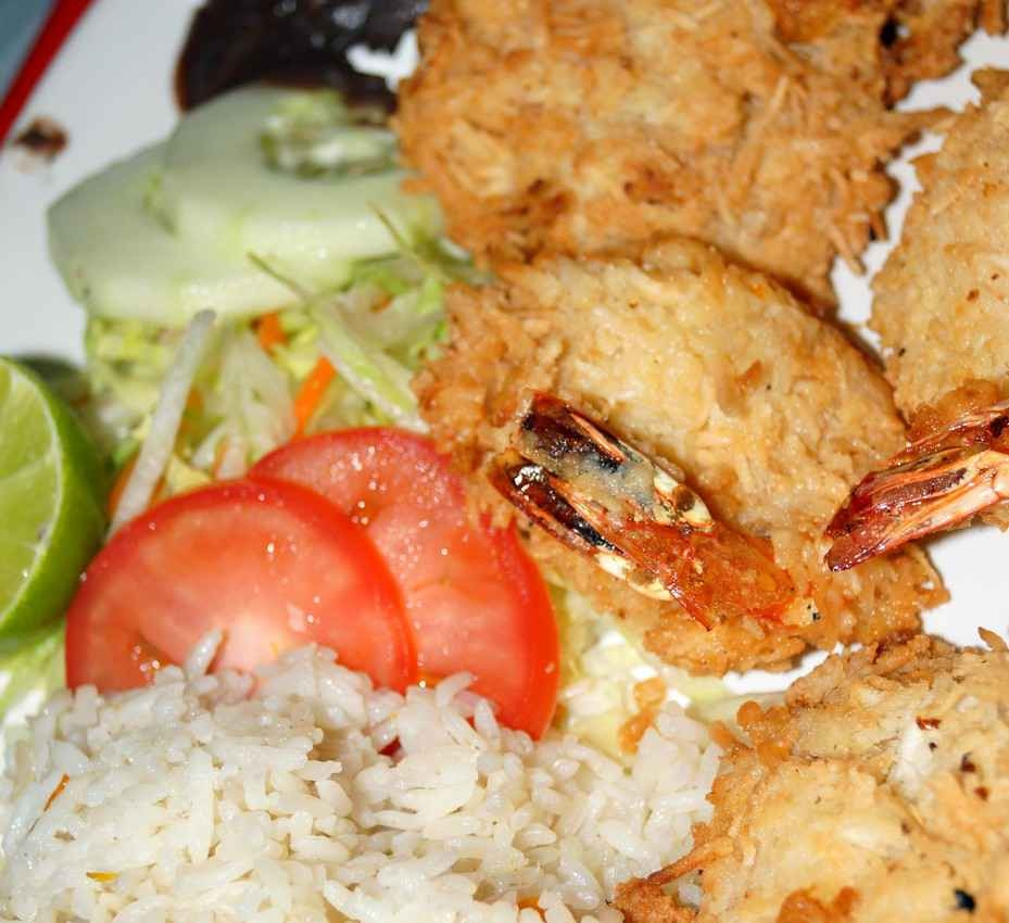 A plate with shrimp and vegetables with rice.