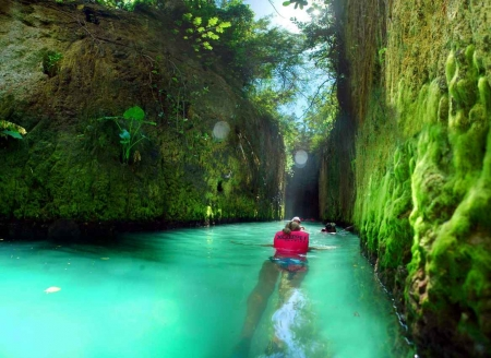 Several people floating down in an underground river at the Xcaret themepark.