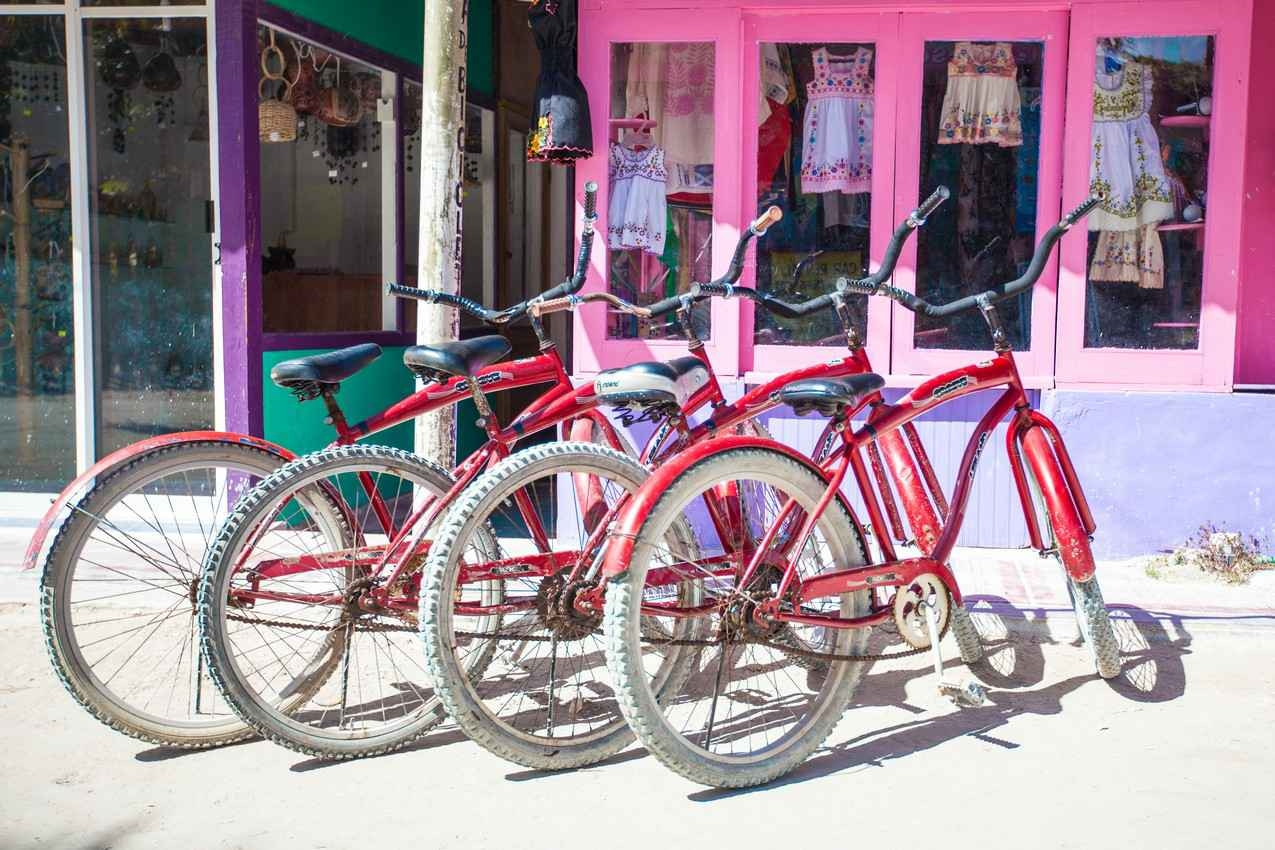Four bikes resting on a sidewalk in Playa Del Carmen.