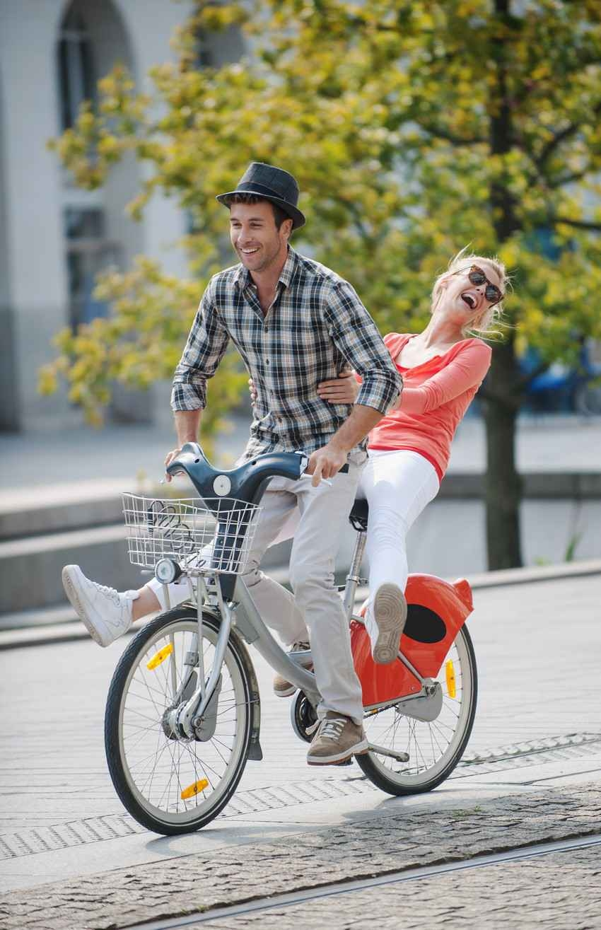 A man and a woman riding a bike together.