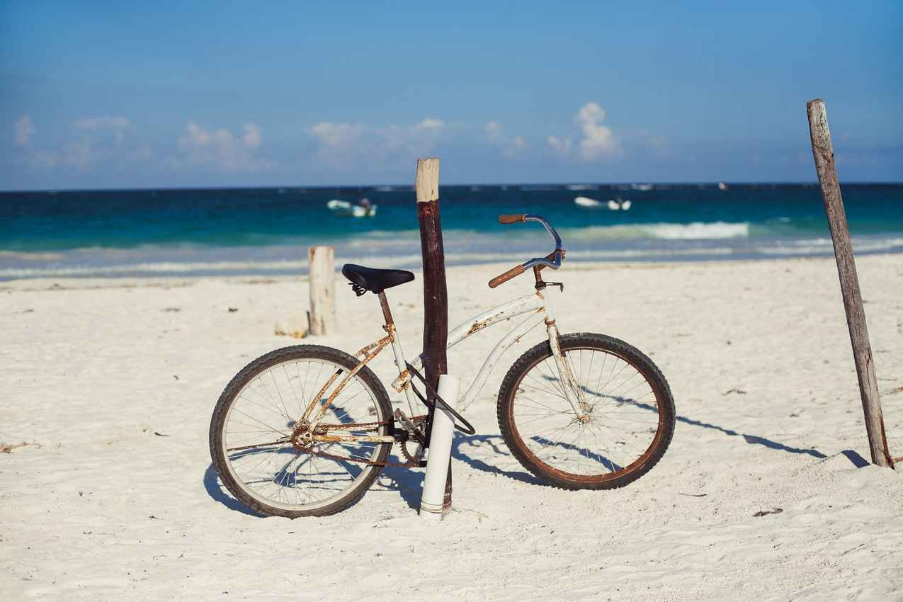 An old and rusty bike that is chained to a wooden post on the beach.