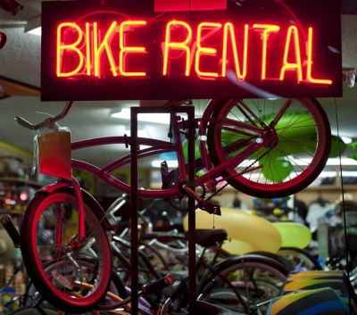 A bike rental neon sign in a shop.