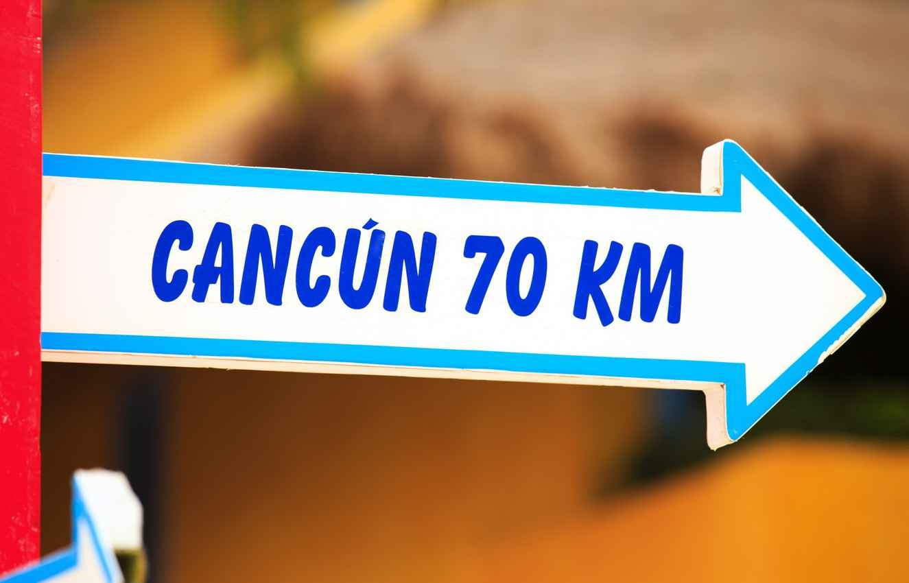 A sign that says Cancun 70 km.