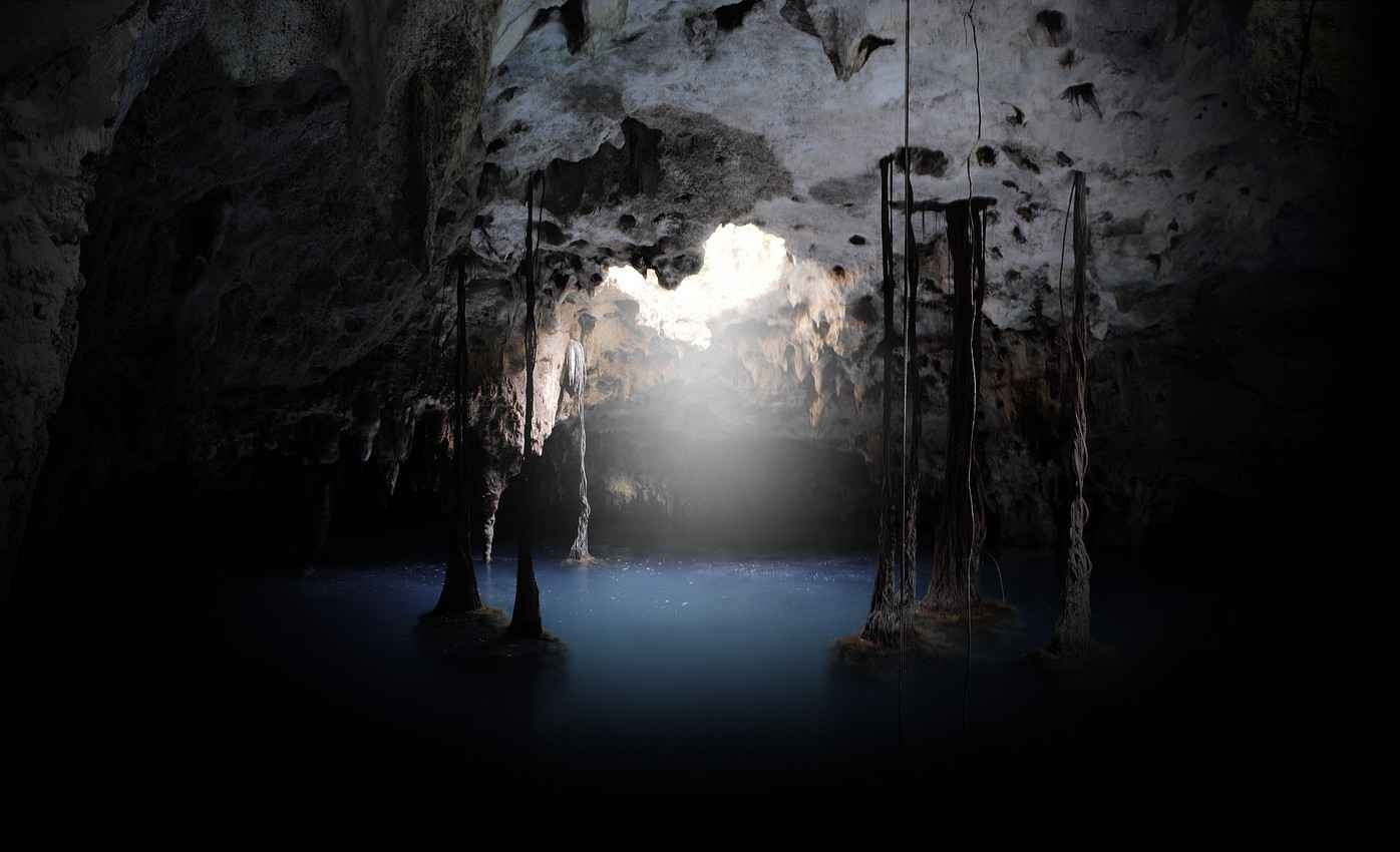 A view of the crystal clear blue water and sunlight shining in a Playa Del Carmen cenote.