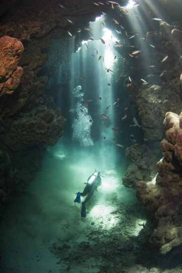 Several scuba divers deep inside an underground cenote.
