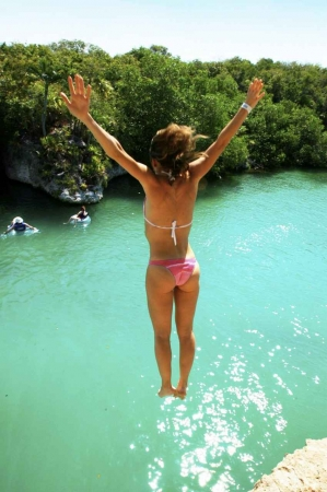 "A cute woman in a bikini jumping off the ""Cliff of Courage."""