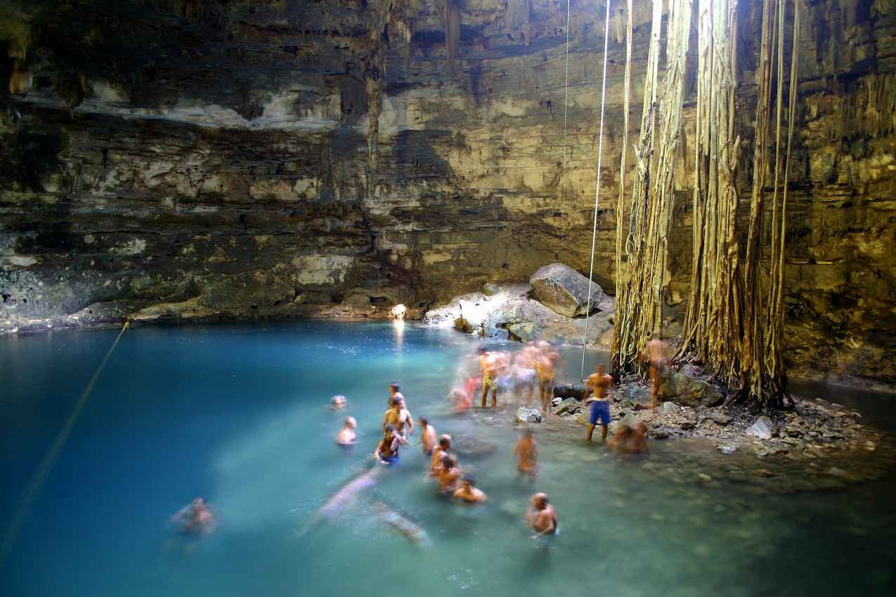 A group of people swimming and playing inside a cenote.