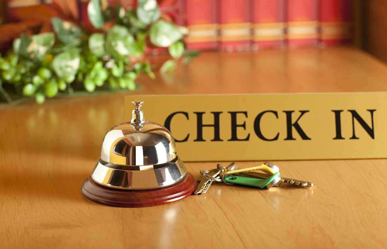 A reception desk check-in and service bell with several room keys next to it.