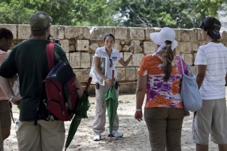 A Chichen Itza tour guide explaining the history of the Mayan ruins.