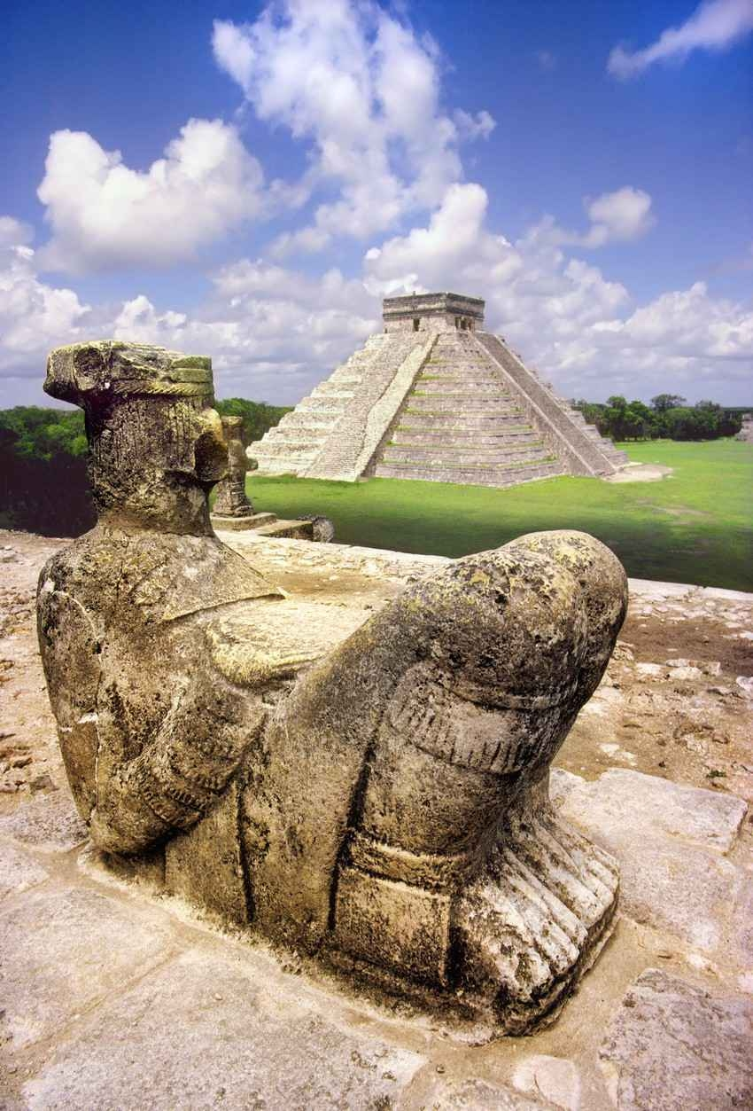 A statue of a Mayan king near one of the large pyramids.