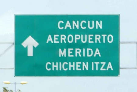 A Cancun airport sign on the freeway.