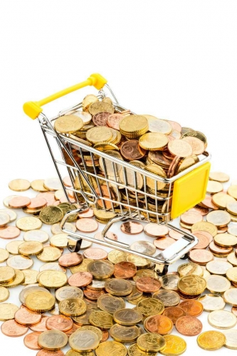 A miniature shopping cart that is full of coins.