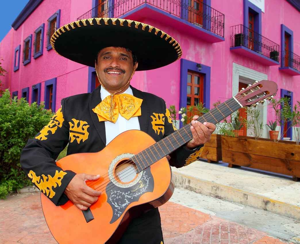 A marriachi singer playing on the street in front of an array of eclectic and colorful buildings.