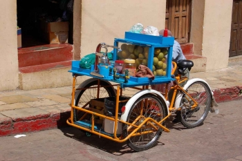 A street food seller who is riding a three wheeled bicycle.