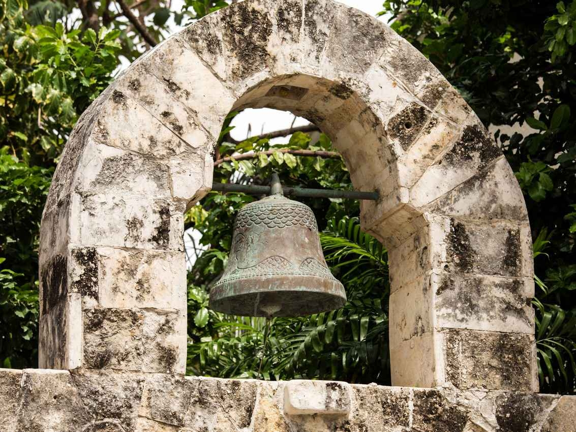An old and antiquated bell that is hanging from a stone arch in downtown Playa Del Carmen.