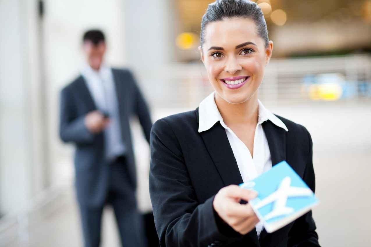 A woman handing a ticket to a passenger at an airport.