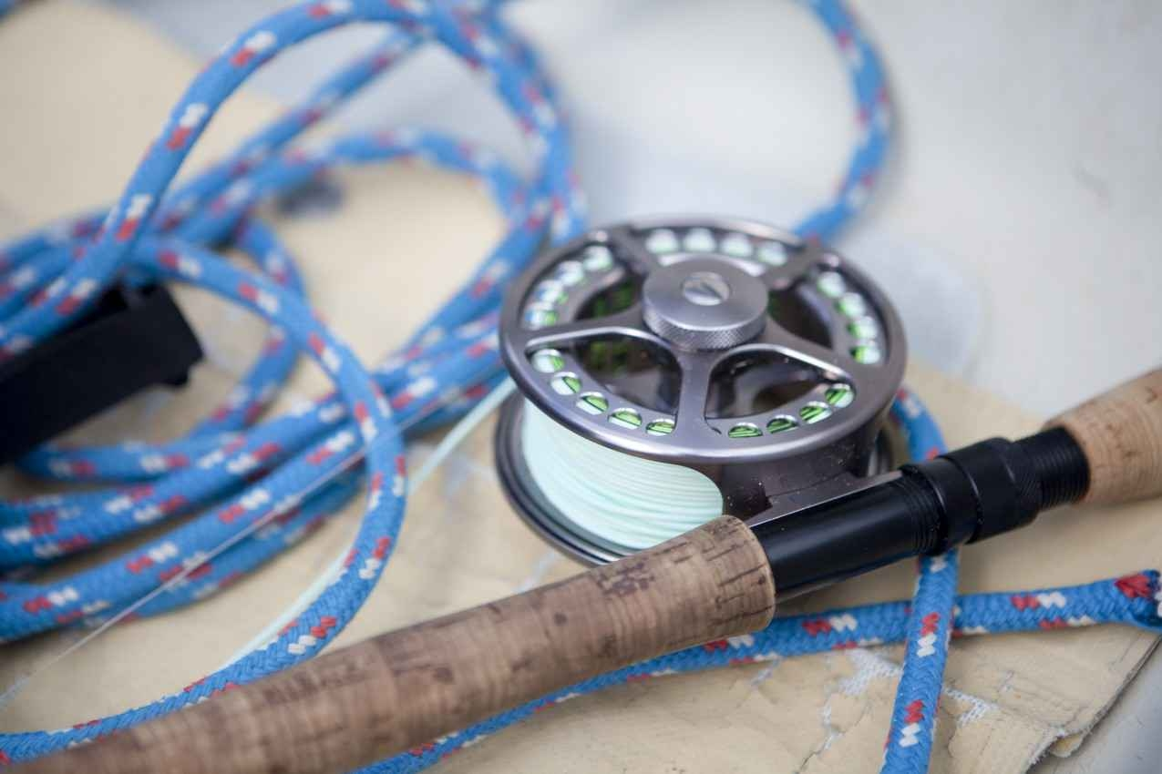 A fly fishing rod and reel on the beach.