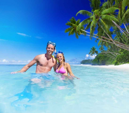 A man and a woman snorkeling in shallow tropical waters.
