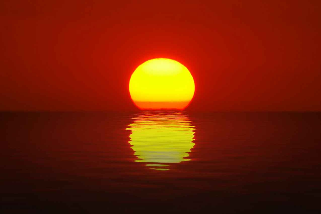 The sun setting and melting into the Caribbean Sea.