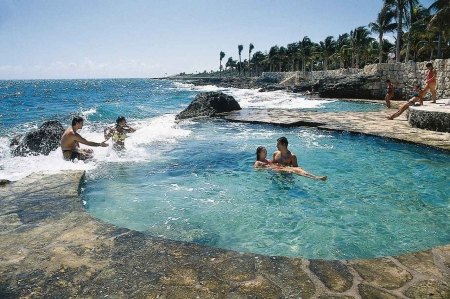 Two men and two women enjoying the beautiful weather at a Playa Del Carmen beach.