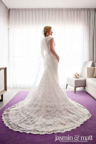 A bride showing off her wedding dress in resort or hotel room.