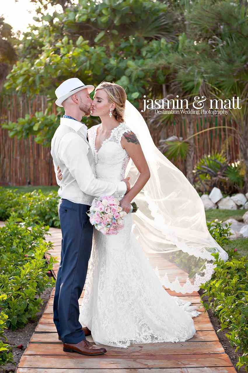 A groom and bride kissing while standing on some wooden planks.