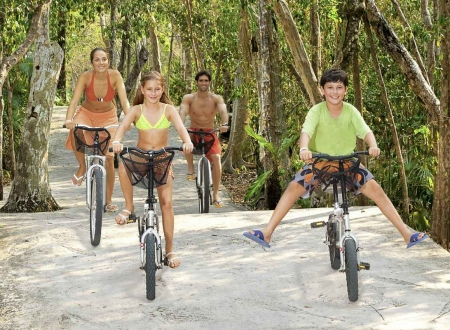 A family of four riding bikes on a jungle road tour.