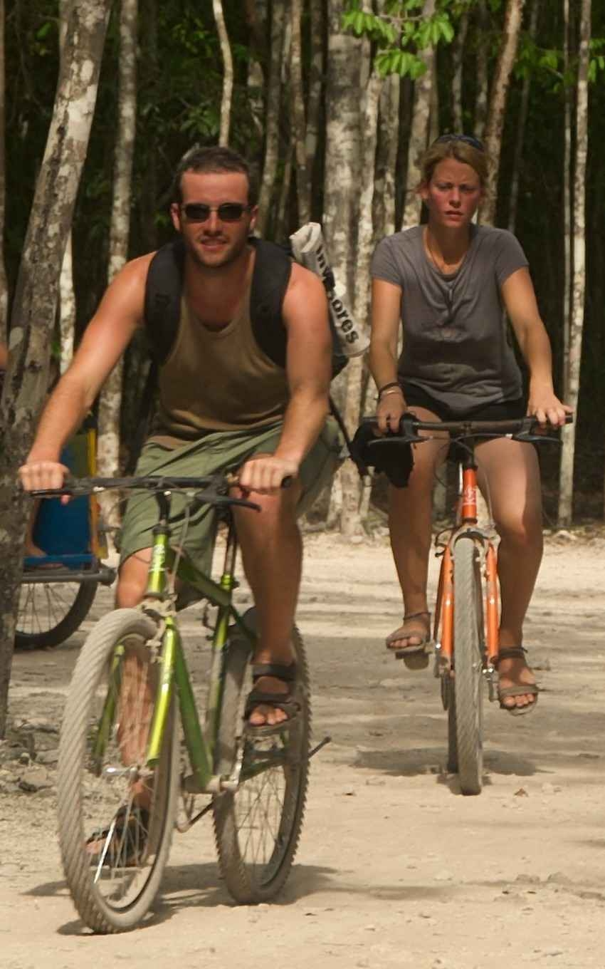 A man and a woman riding bikes on a jungle trail.