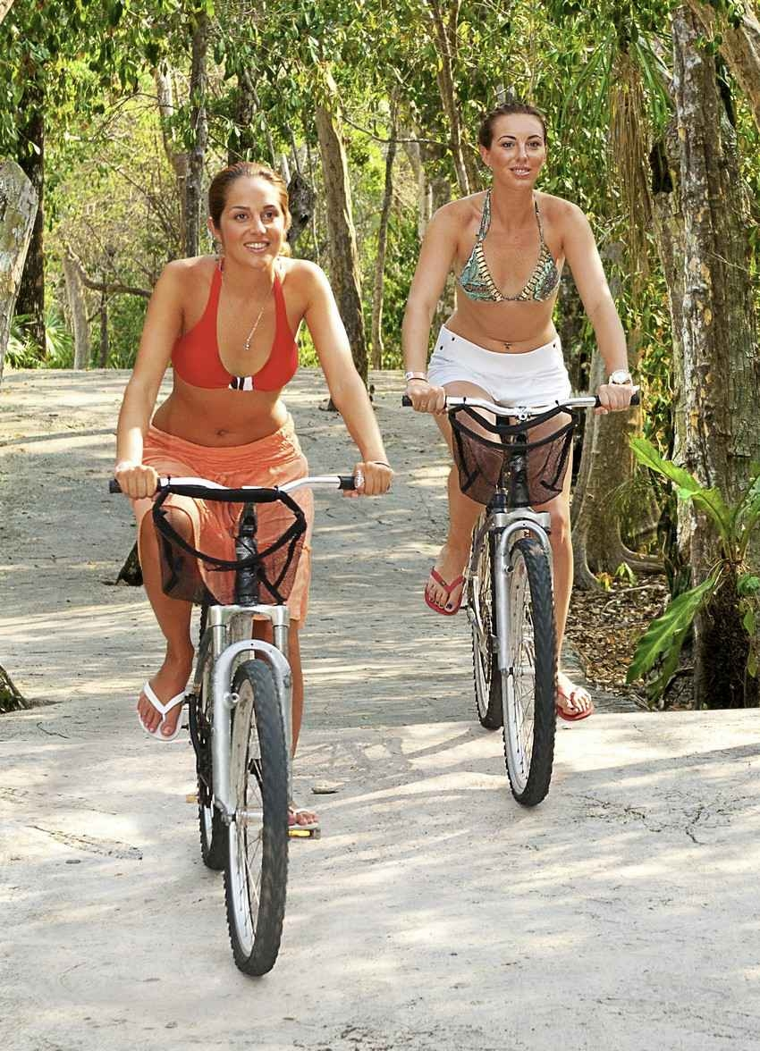 Two amazingly hot women riding bikes in the jungle.
