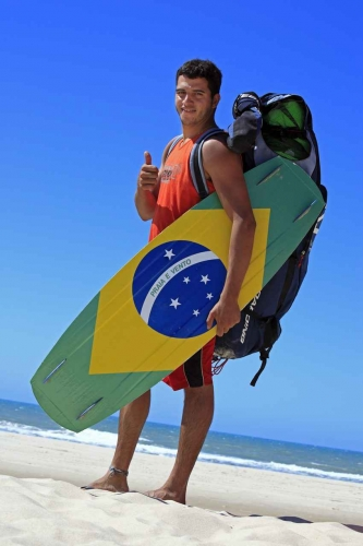 A Brazilian man holding a kite board with a Brazilian flag.