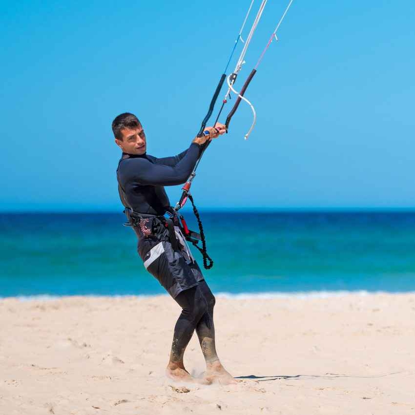 A man standing on a Playa Del Carmen beach testing his kite board.