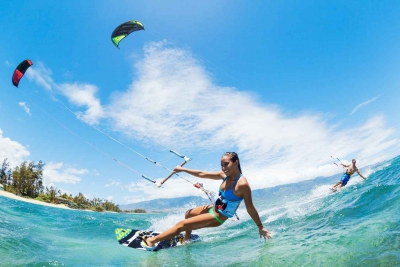 A man and a woman kite boarding in the Caribbean Sea.