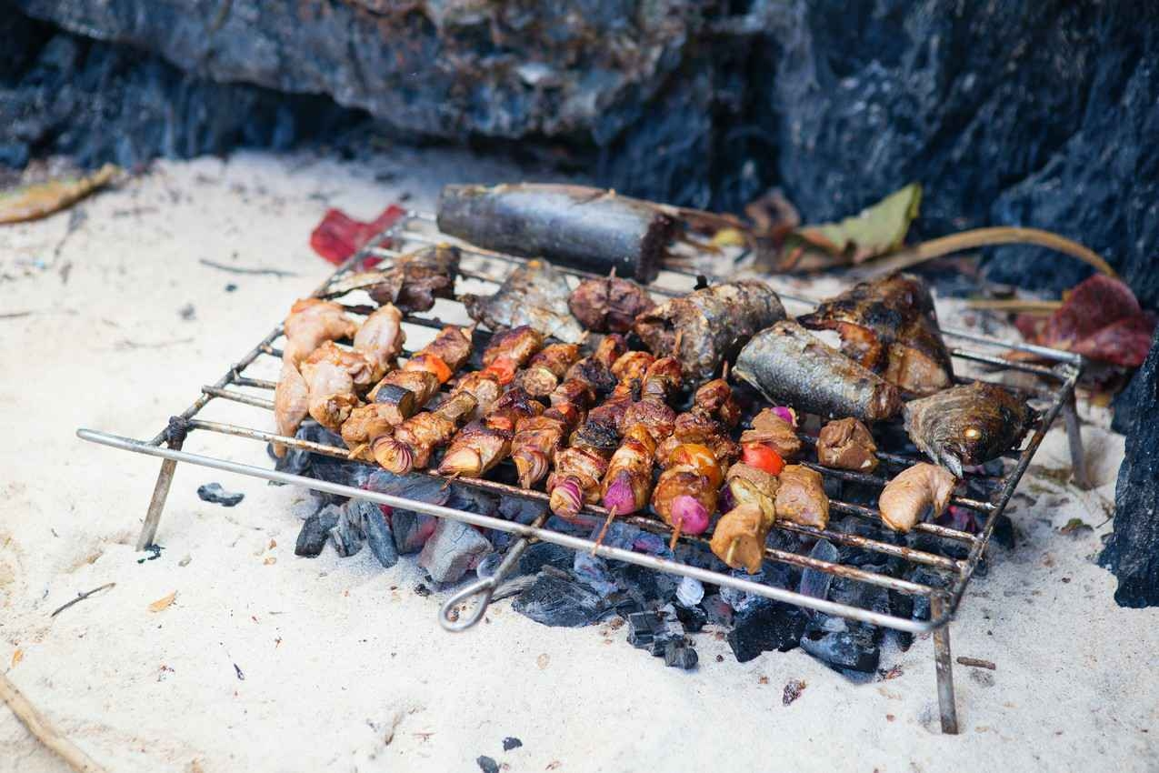 Fish and several kebabs cooking on an open air charcoal grill.