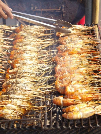 Several large shrimp cooking on a charcoal grill.