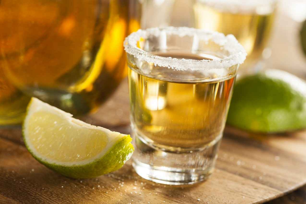 A tequila shot that has a salted rim with several limes on the side of the shot glass.