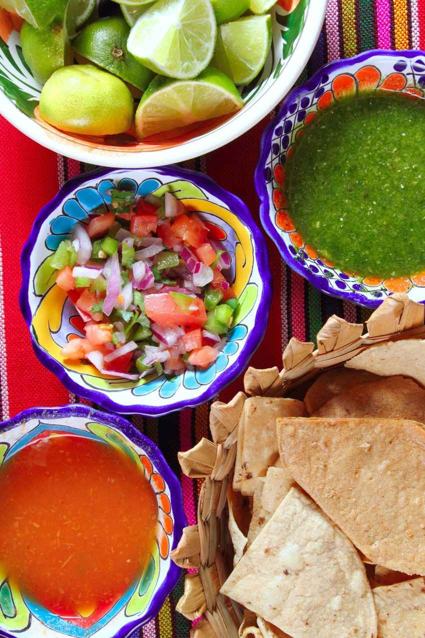 Three types of Mexican salsa with lines and corn chips on the side.