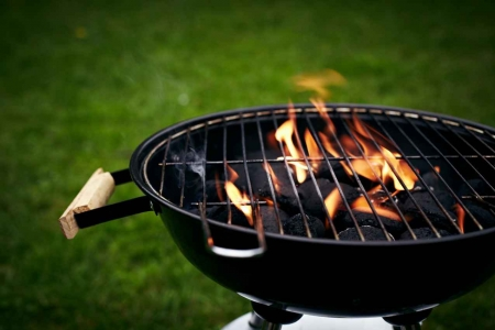 A charcoal grill burning with a large flame in a grassy backyard.