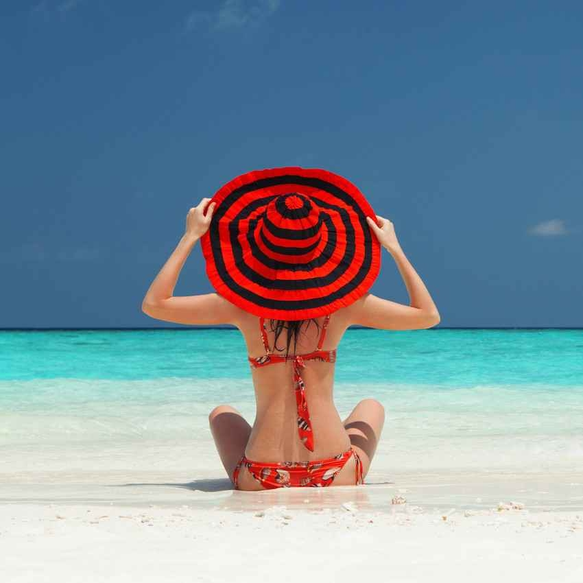 A very sexy woman on the Playa Del Carmen beach with a large red hat and a red bikini.