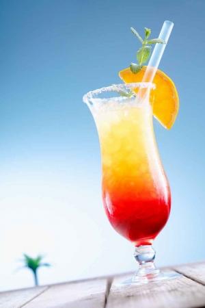 A tequila sunrise on a wooden table near the beach.