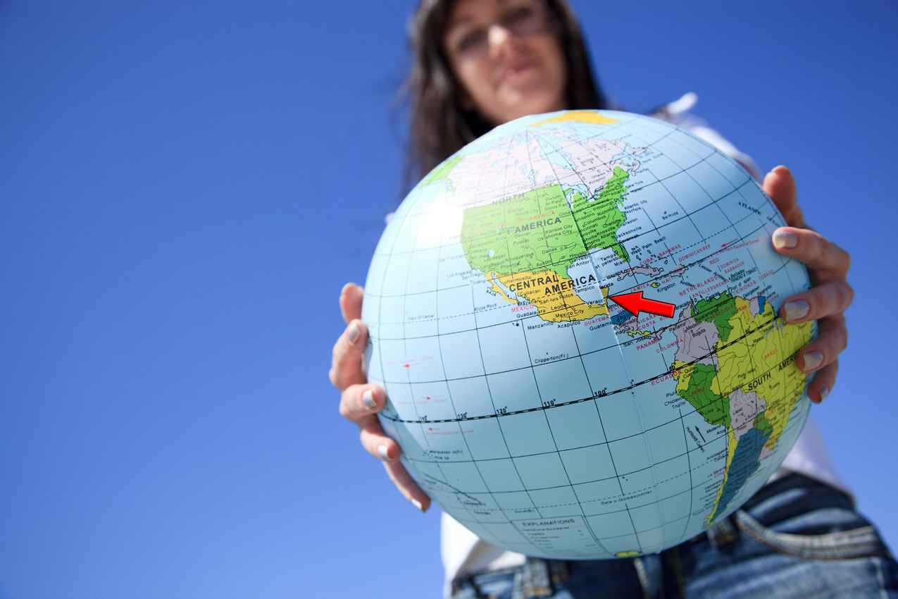 A woman holding a globe with Playa Del Carmen center.