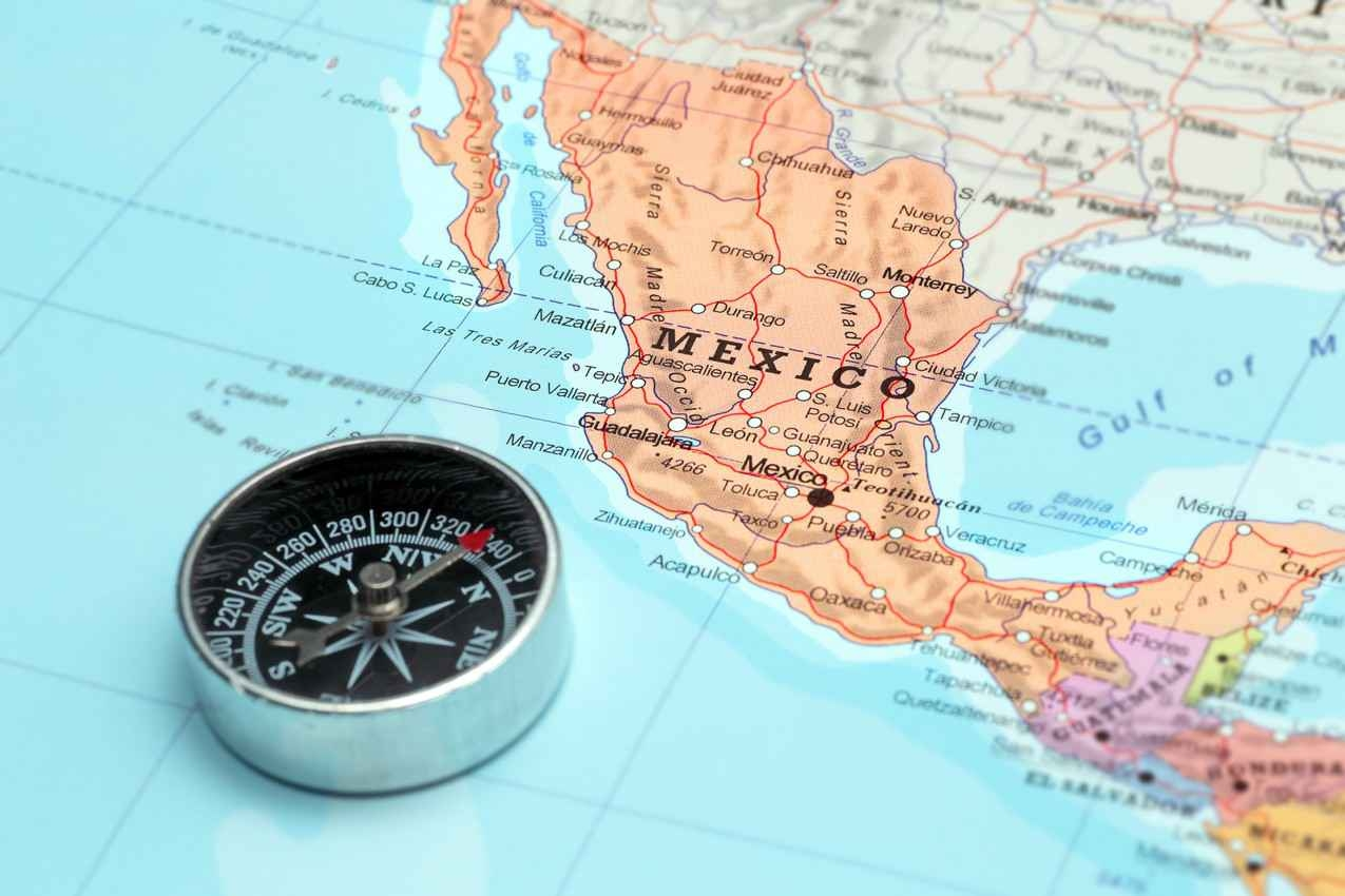 A Mexican map with a compass on top of it.